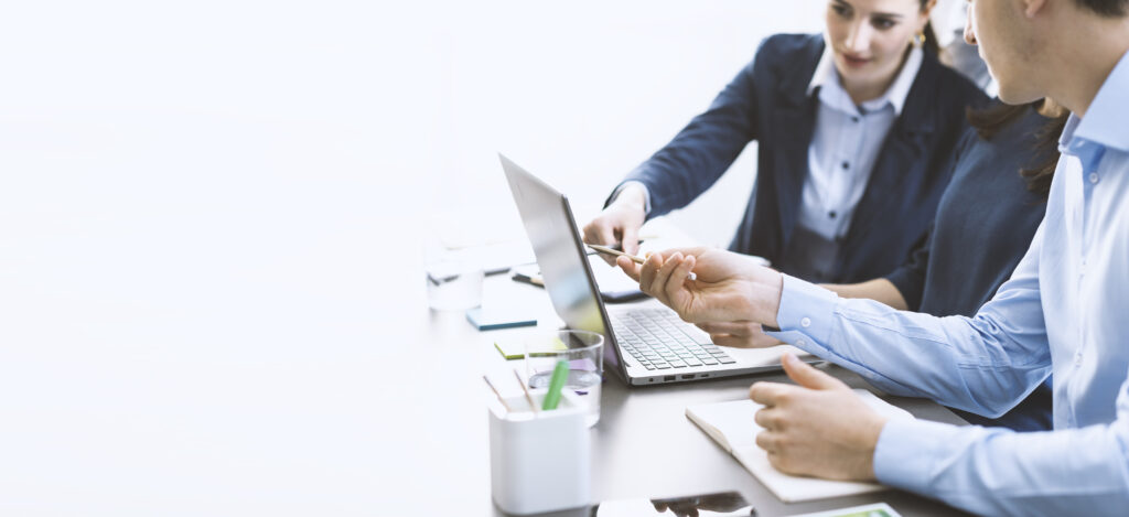 Businessman en -vrouw zitten naast elkaar te werken een te overleggen met een laptop voor zich